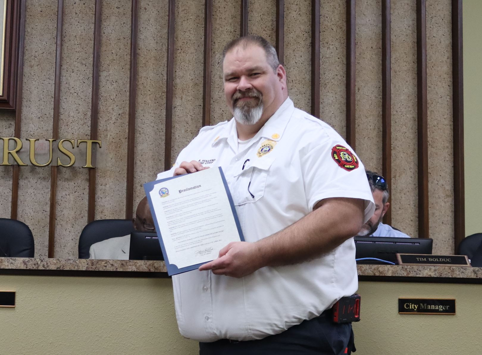 Crestview Fire Chief Tony Holland displays a proclamation from Mayor JB Whitten honoring dispatchers