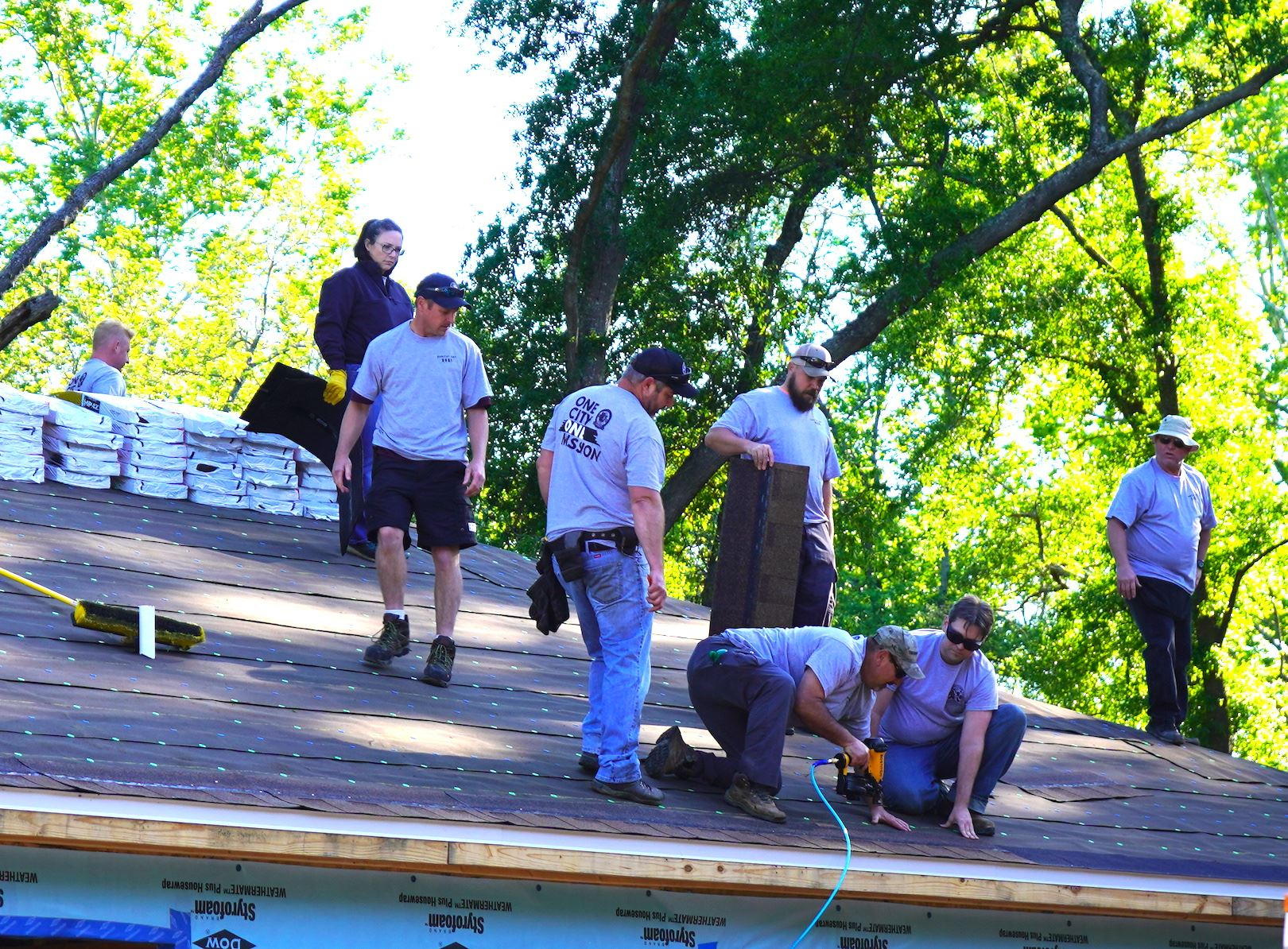 City employee volunteers take to the rooftop to shingle a Habitat for Humanity house.