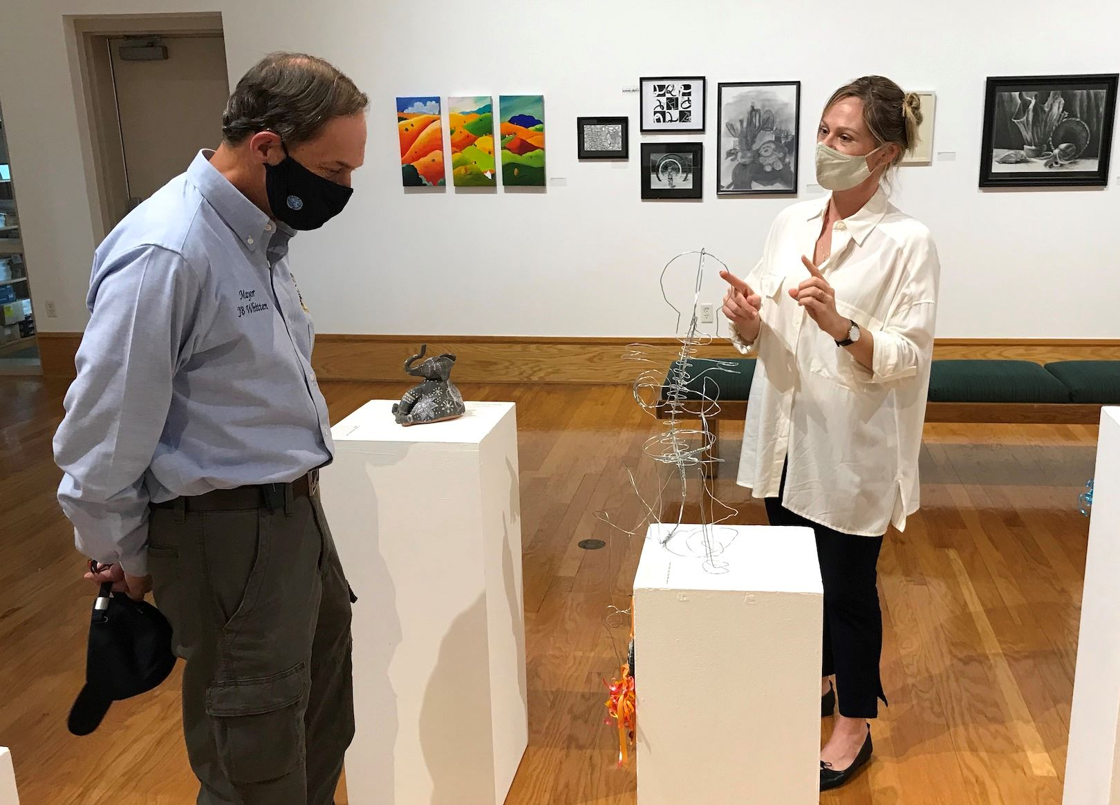 Mayor JB Whitten admires student works at NWF State College's galleries with director Wren Supak.